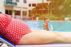 Pregnant mother relax while kid play with water. Pregnant mother relax by the pool while kid play with water Stock Photos