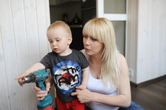 Pregnant mother shows to the little son the tool for crackdown Stock Photo