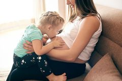 Pregnant mother sitting with cute daugher kissing big belly stock photography