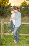 Pregnant mother sitting her son on a wooden fence in a field Stock Photography