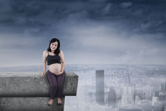 Pregnant mother sitting on rooftop Stock Photos
