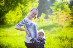 Pregnant mother with small daughter outdoors. Pregnant mother with her small daughter outdoors Royalty Free Stock Photo
