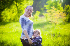 Pregnant mother with small daughter outdoors. Pregnant mother with her small daughter outdoors Royalty Free Stock Image