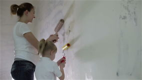 A pregnant mother and a small daughter painting a wall with rollers. A young pregnant mother and a small blond-haired daughter smearing glue a white wall with stock video footage