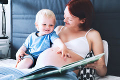 Pregnant mother and son at home. Pregnant mother and son are talking and reading book together in bed at home. Little child boy looking at her mother pregnant Royalty Free Stock Image