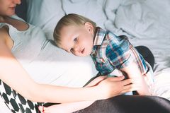 Pregnant mother and son at home. Pregnant mother and son are talking and spending time together in bed at home. Little child boy looking at her mother pregnant Stock Photo