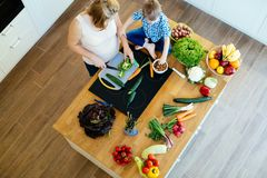 Pregnant mother and son preparing meal stock images