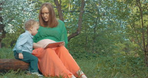 Pregnant mother and son with tablet PC outdoor stock video footage