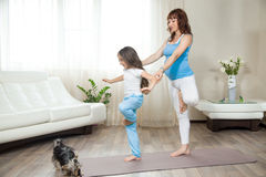 Pregnant mother teaching her kid girl yoga at home. Family healthy lifestyle concept. Pregnancy Yoga and Fitness. Young happy pregnant yoga mom working out with royalty free stock photo