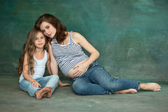 Pregnant mother with teen daughter. Family studio portrait over blue background. Teenager girl hugs her lovely mom Stock Image