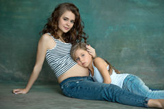 Pregnant mother with teen daughter. Family studio portrait over blue background. Teenager girl hugs her lovely mom Royalty Free Stock Photo