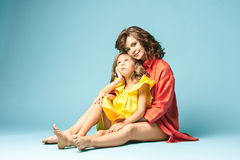 Pregnant mother with teen daughter. Family studio portrait over blue background. Teenager girl hugs her lovely mom Stock Images