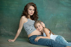 Pregnant mother with teen daughter. Family studio portrait over blue background. Teenager girl hugs her lovely mom Stock Photography