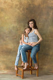Pregnant mother with teen daughter. Family studio portrait over blue background. Teenager girl hugs her lovely mom Royalty Free Stock Image