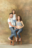 Pregnant mother with teen daughter and husband. Family studio portrait over brown background. Teenager girl hugs her lovely mom Royalty Free Stock Images