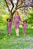 A pregnant mother and two curly daughter playing in  park stock images