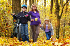 Pregnant mother walking in the park with her son and daughter. Pregnant mother walking with her son and daughter in the autumn forest stock photography