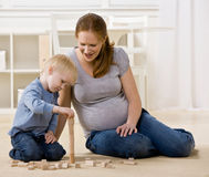Pregnant mother watches son stack wooden blocks Royalty Free Stock Photo