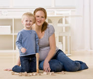 Pregnant mother watches son stack wooden blocks royalty free stock images