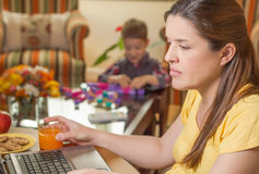 Pregnant mother working in home office with son. Pregnant mother working in home office with notebook and his boring son playing on the background royalty free stock photos