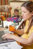 Pregnant mother working in home office with son Royalty Free Stock Images
