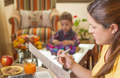 Pregnant mother working in home office with son. Pregnant mother reading business documents in a home office and his boring son playing on the background stock images