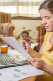 Pregnant mother working in home office with son. Pregnant mother reading business documents in a home office and his boring son playing on the background royalty free stock image