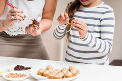 Pregnant mum and her little daughter baking together Stock Image