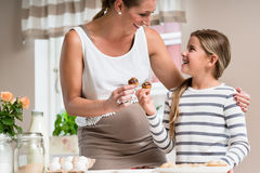 Pregnant mum and her little daughter baking together Stock Photos