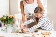 Pregnant mum and her little daughter baking together Royalty Free Stock Photos