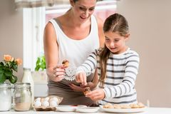 Pregnant mum and her little daughter baking together Royalty Free Stock Image