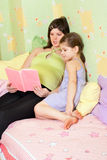 Pregnant mum reads the book of the daughter Stock Photography