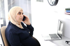 Pregnant Muslim Arabic business woman. Working at office Royalty Free Stock Photography