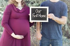 Pregnant new family buying their new home holding our first home sign. Homeowners Pregnant mom and dad holding sign for our first home for new first home in royalty free stock photo