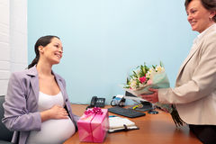 Pregnant office worker going on maternity leave. Royalty Free Stock Images