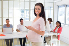 Pregnant office worker touches bump and texts on phone and smiles at camera Royalty Free Stock Photos