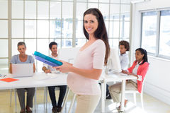Pregnant office worker walking with folders Royalty Free Stock Photography