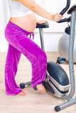 Pregnant preparing for workout on bicycle. Closeup Stock Images
