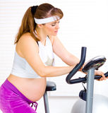 Pregnant preparing for workout on stationary bike Royalty Free Stock Photography