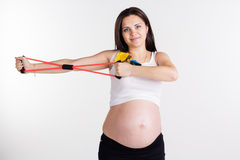 Pregnant pretty woman doing sport with resistance Stock Images