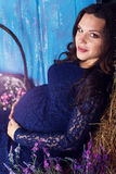 Pregnant pretty woman with flowers in studio Royalty Free Stock Photography
