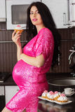 Pregnant pretty woman in kitchen eating sweet Royalty Free Stock Photos