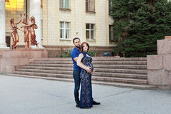Pregnant red hair woman in long blue dress and stylish man Stock Photos
