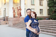 Pregnant red hair woman in long blue dress and stylish man Royalty Free Stock Photography