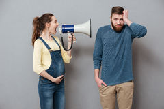Pregnant screaming woman holding loudspeaker near confused man Stock Photo
