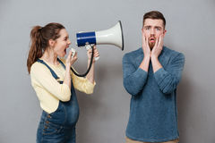 Pregnant screaming woman holding loudspeaker standing near man Royalty Free Stock Photos