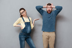 Pregnant serious woman standing near screaming man Royalty Free Stock Photos
