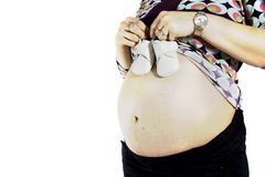 Pregnant showing baby shoes royalty free stock photography