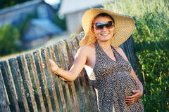 Pregnant smiling woman in field. Young pregnant smiling woman at sunset in the summer field royalty free stock photo