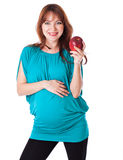 A pregnant smiling woman is holding an apple. In her hand. Isolated on a white background Royalty Free Stock Images
